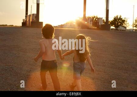 Geschwister, die Hand in Hand an Tankstelle Stockbild