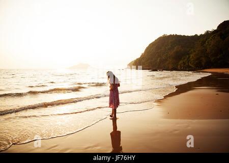 Mädchen am Strand, Sonnenuntergang. Stockbild