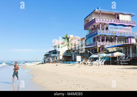 Sri Lanka, Asien, Hikkaduwa - ein gebürtiger Mann am Strand laufen Stockbild