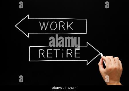 Hand schreiben Arbeit und Ruhestand auf zwei Pfeile mit Kreide auf Tafel. Konzept über die Entscheidungsfindung der alternden Arbeitnehmer zwischen weiter arbeiten oder Stockbild