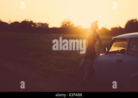 Frau mit einem retro Auto im Sommer Sonnenuntergang Stockbild