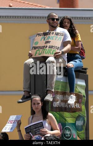 """Schüler gesehen, die ein Plakat auf einer Werbung vor dem portugiesischen Parlament sitzt, während des Protestes. Tausende von portugiesischen Studenten Verband der internationalen Bewegung """"Freitags für Zukunft"""" in Lissabon gegen die Klimaproblematik zu protestieren. Dieser Streik zielt darauf aufmerksam die politischen Führer der Welt auf die Schwere der Klimaproblematik. Stockbild"""