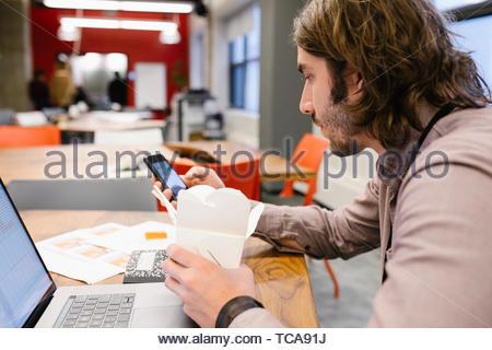 Geschäftsmanns, der spät, Essen essen im Büro Stockbild