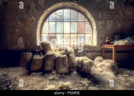Innenansicht mit Taschen aus Wolle vor einem Fenster in einer verlassenen Fabrik in Belgien. Stockbild