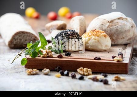 Gesäter Brötchen und rustikale Brote auf Schneidebrett, still life Stockbild
