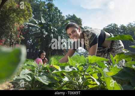 Lächelnde Frau im ländlichen Landwirtschaft Feld zusammen mit ihrer Tochter an einem sonnigen Tag. Stockbild