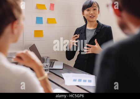 Geschäftsfrau, die von einer Mauer mit Haftnotizen führt eine Geschäftspräsentation stehen. Stockbild
