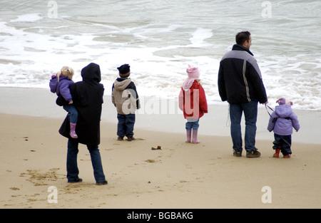 Familie am Strand mit Blick auf das Meer Stockbild