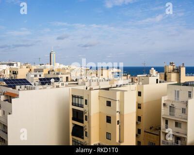 Blick über die Dächer in den dicht bebaut und bevölkert Saint Julians in Malta, auf das blaue Mittelmeer mit dem Casino inn Die mi Stockbild