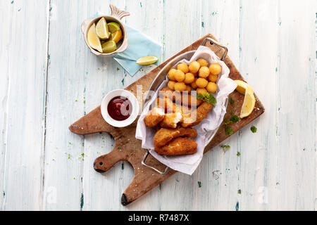 Käse Kroketten aus Kartoffeln und Kugeln auf Schneidebrett mit Tomatensauce, Stillleben, Ansicht von oben Stockbild