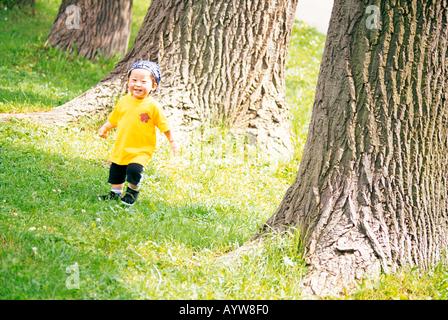 Ein kleiner Junge von großen Bäumen Stockbild