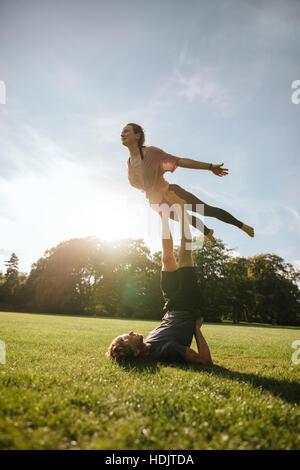 Vertikale Aufnahme des Fit junges Paar akrobatische Yoga zu tun. Mann auf dem Rasen liegen und balancing Frau in Stockbild