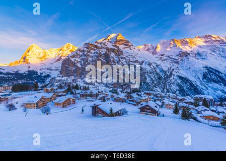 MüRren, Berner Oberland, Kanton Bern, Schweiz. Das Dorf mit Eiger, Mönch und Jungfrau im Hintergrund bei Sonnenuntergang Stockbild