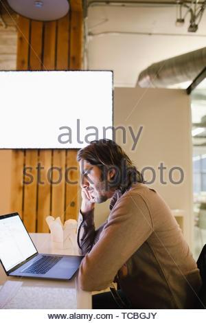 Konzentrierte Geschäftsmann spät am Laptop arbeiten Stockbild