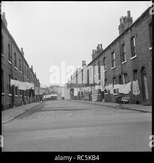 Burmantofts, Leeds, West Yorkshire, 1966-1974. Wäsche aufhängen zwischen Rücken an Rücken Häuser in Westlock Terrasse oder Westlock Halbmond mit einem Burton Emblem sichtbar an der Wand am Ende der Straße umschließenden Montague Burton's Hudson Road Mühlen. Stockbild