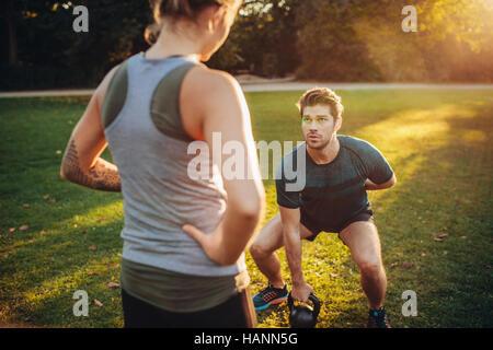 Weibliche Trainer Mann während des Trainings mit Kettlebell im Park führen. Personal Trainer mit Mann Stockbild