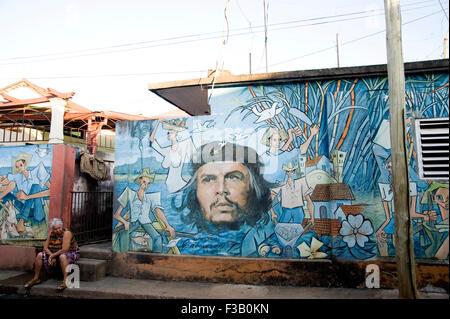 Alte Dame sitzt neben Che Guevara Wandbild in Baracoa, Kuba Stockbild