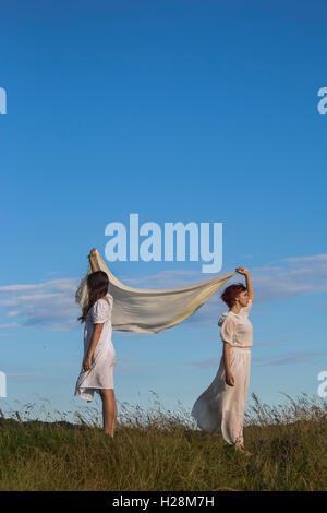 zwei Mädchen in weißen Kleidern halten einen Schal in den wind Stockbild