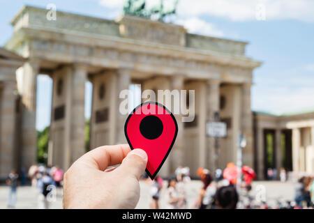 Nahaufnahme der Hand eines jungen kaukasischen Mann mit einer roten Markierung in der beliebten Brandenburger Tor in Berlin, Deutschland Stockbild