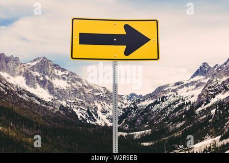 Richtungspfeil Zeichen in einer schneebedeckten Bergwelt. Stockbild