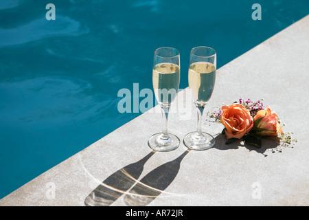 Sektgläser neben Schwimmbad Stockbild