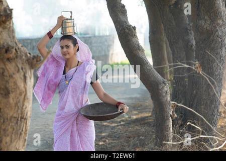 Ländliche Frau zur Arbeit zu gehen, die Ihr tiffin Box auf den Kopf und ein Bügeleisen Gold Pan in der Hand. Stockbild