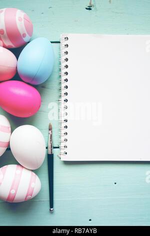 Ein wunderschönes und farbenfrohes Close-up Flat von isolierten Ostereier in Unifarben und gestreifte Neben Notebook mit Raum über ein Pastell blau Holztisch Stockbild