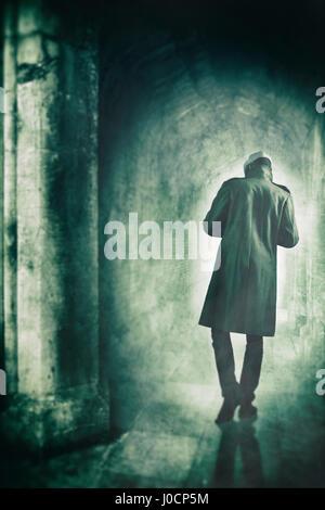 Mann zu Fuß entfernt von der Kamera in einen nebligen tunnel Stockbild