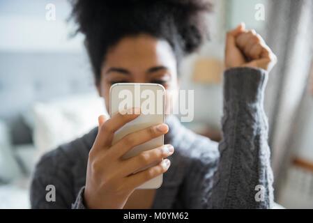 Afrikanische amerikanische Frau feiern, während SMS auf Handy Stockbild