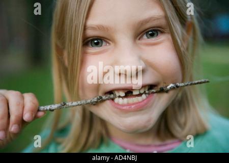 Ein junges Mädchen mit einem fehlenden vorderen Zahn beißen einen Stock Stockbild