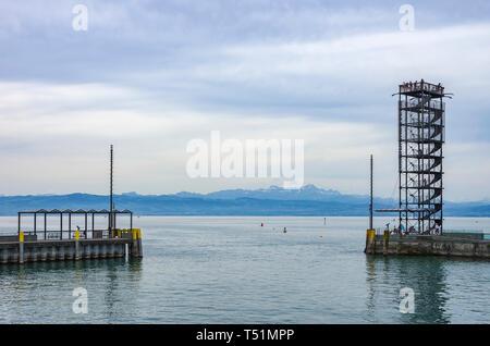 Hafeneinfahrt mit Aussichtsturm, Friedrichshafen, Deutschland, mit Blick auf den Bodensee und die Schweizer Alpen. Stockbild