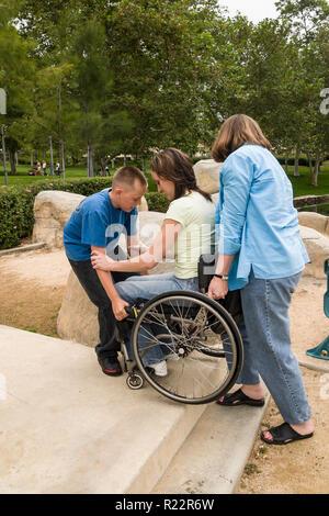 Junge Helfen seiner Tante seiner Mutter heben Sie einen Schritt in den Park. Herr © Myrleen Pearson... Ferguson Cate. Serie von 4 Bildern Stockbild