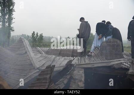 Kaschmir Männer gesehen, dass ein Krieg verwüsteten Haus nach einem gunbattle in Pulwama, südlich von Srinagar. Zakir Ahmed Rashid Bhat Alias Musa war spät am Donnerstag durch die Sicherheitskräfte in Pulwama Bezirk getötet, als Sicherheitskräfte ein Cordon und Suchen in Dadsara Dorf zentralen Bereich gestartet hatte, südlich von Srinagar nach Informationen über militante Präsenz. Stockbild