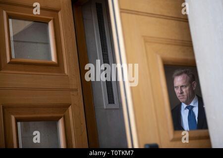 In den USA, die US-Verteidigungsminister Patrick Shanahan Peaks aus der Haustür Fenster, wie er für die Ankunft von Präsident Donald Trump am Pentagon am 15. März 2019 in Washington, D.C. wartet Stockbild
