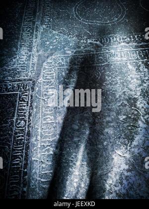 Unheimliche Schatten auf alten Grabstein in der Kirche. Konzept des Todes, Krimi und Horror. Stockbild