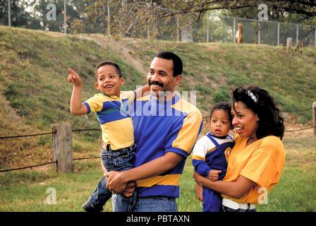 Junge Familie gemeinsam draußen im Park genießen jeden anderen MR © Myrleen Pearson.... Ferguson Cate Stockbild