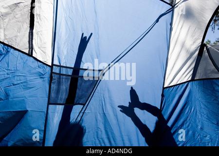 Kinder machen Schattenfiguren hinter einem Zelt Stockbild