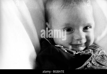 Foto von Mädchen Tochter schwarz weißes körniges Lächeln Kinderbett UK Stockbild