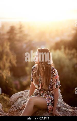Gemischte Rassen Frau sitzt auf Fels Stockbild