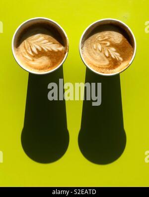 Zwei Cappuccinos mit Schatten am grünen Tisch Stockbild
