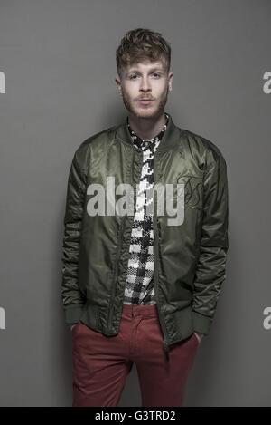 Studio-Porträt eines bärtigen jungen Mannes trägt eine grüne Bomber-Jacke. Stockbild