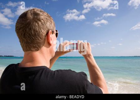 Rückansicht eines Mannes mit einer digitalen Kamera, Cable Beach, Nassau, Bahamas, Caribbean Stockbild