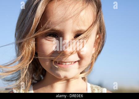 Junges Mädchen mit Haaren im Gesicht weht Stockbild