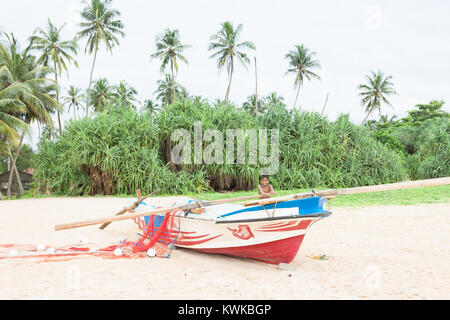 Asien - Sri Lanka - induruwa - ein Fischer Junge spielt mit einem Boot Stockbild