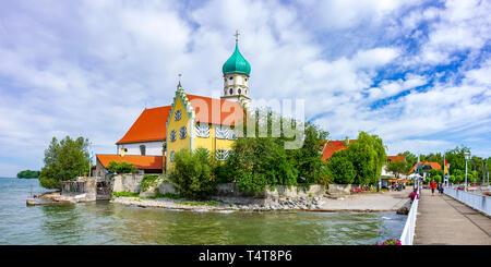 Blick auf St. George's Kirche und der Pier mit Touristen in Wasserburg am Bodensee, Bayern, Deutschland. Stockbild