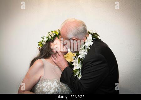 Ältere Braut und Bräutigam küssen bei Hochzeit Stockbild