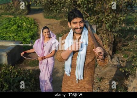 Bauer oder Dorf Mann, der für die Landwirtschaft Feld mit einem Spaten mit seiner Frau folgt ihm mit einem Eisen Gold Pan in der Hand. Stockbild