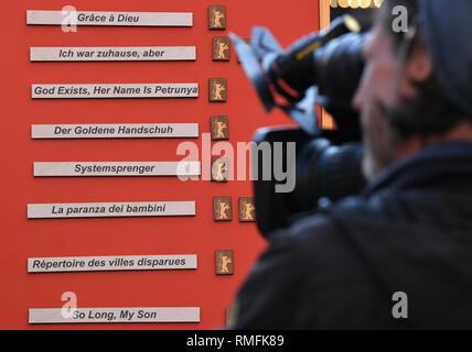 Berlin, Deutschland. 14 Feb, 2019. 69. Berlinale: ein Kameramann Filme eine Tafel, auf der die Titel der einzelnen Filme aus Wettbewerb der Berlinale gesehen werden kann. Foto: Jens Kalaene/dpa/Alamy leben Nachrichten Stockbild