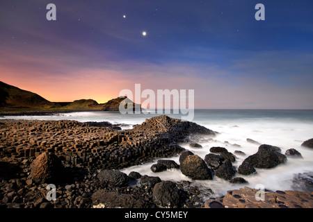 Los Giants Causeway en la noche mostrando conjunción de Venus y Júpiter en el cielo. Imagen De Stock