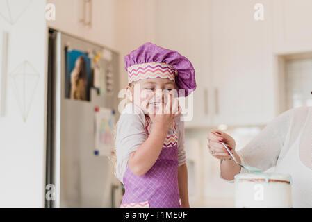 Feliz, linda chica en chefÕs hat bicarbonato en la cocina Imagen De Stock